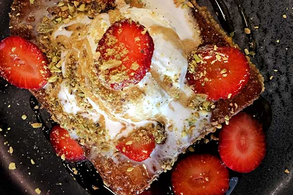 Toast with icecream sprinkled with crushed nuts and strawberries