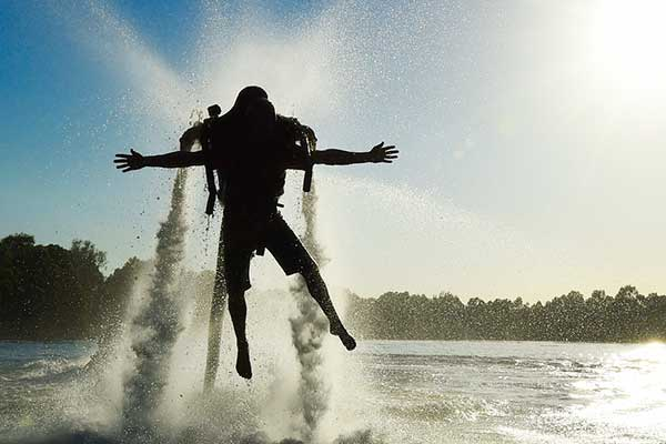 The silhouette of a man up in the air using a water jetpack on a river