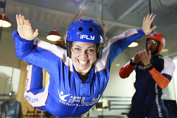 Young woman smiling whilst indoor skydiving