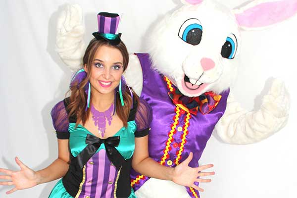 A woman dressed in festive Easter costume accompanied by someone in a rabbit costume.