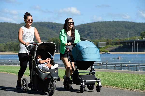 Two young ladies walking on a footpath alongside the water at the Regatta Centre pushing strollers