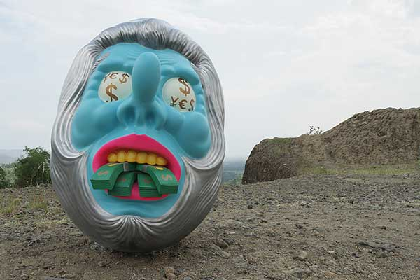 Large mask sculpture with dollar sign eyes and money in it's mouth