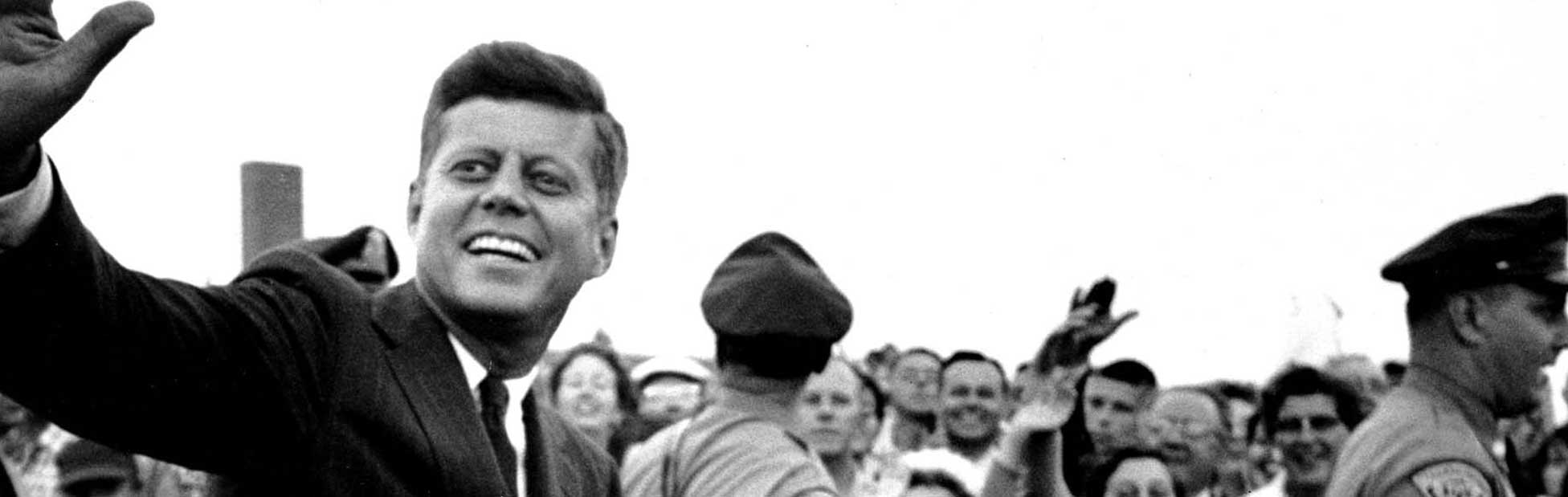 JFK sitting in the back of a car waving to the crowd