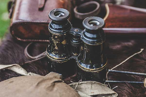 a pair of old binoculars and a leather bag