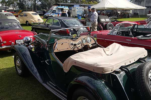 Vintage green convertible automobile surrounded by other display cars