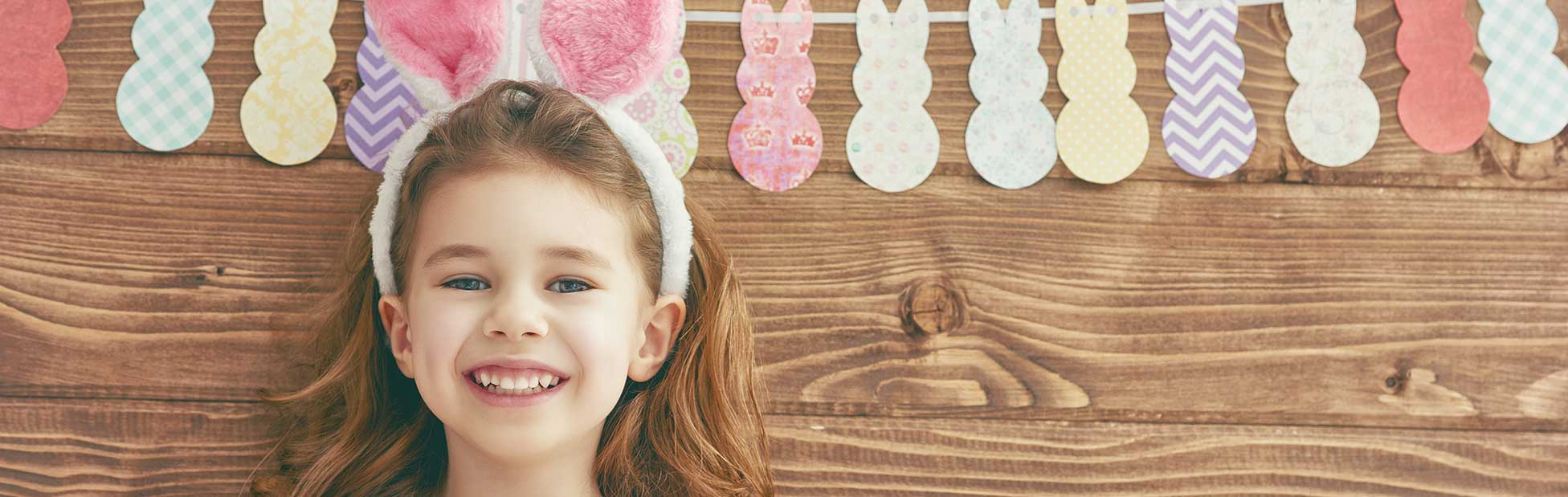 Girl smiling wearing Easter bunny ears