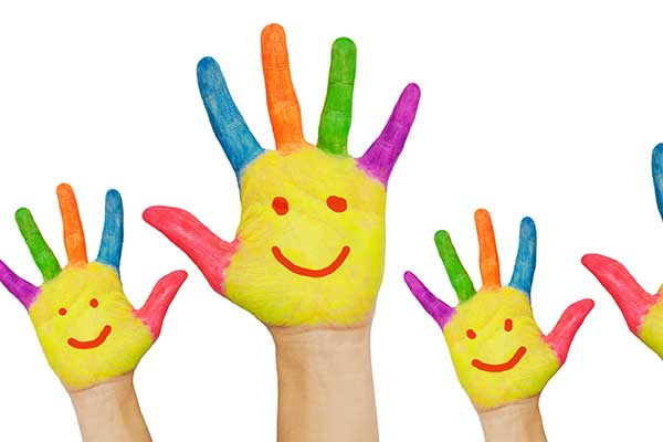 Painted hands with smiley faces waving