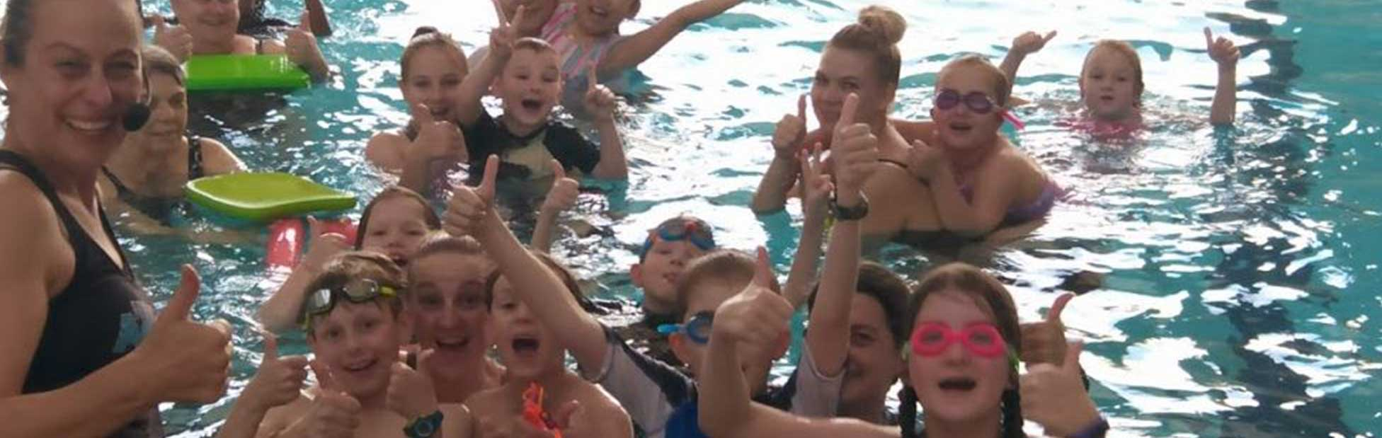 Swim instructor and children in the pool