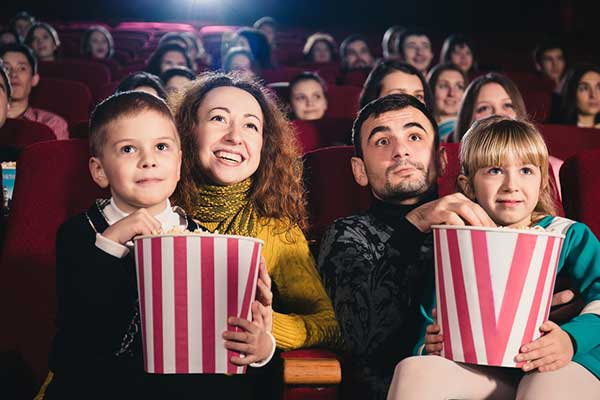 Family watching movie eating popcorn