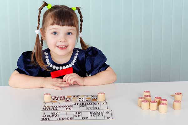 Girl sitting at desk with bingo sheets in front of her