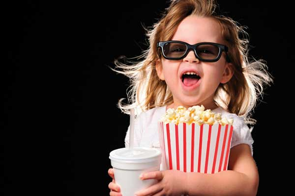 Girl with glasses on holding large popcorn