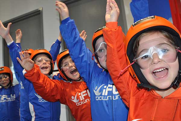 Children dressed to iFLY cheering with hands up