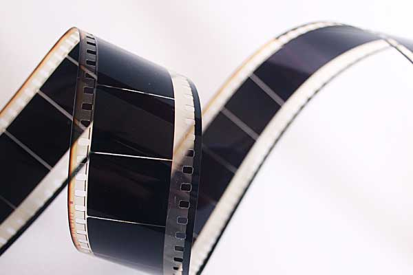 Old style film curled up on white background