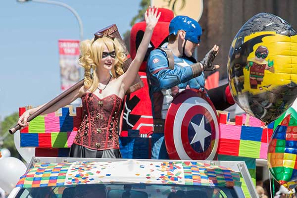 Superheros waving from vehicle in parade