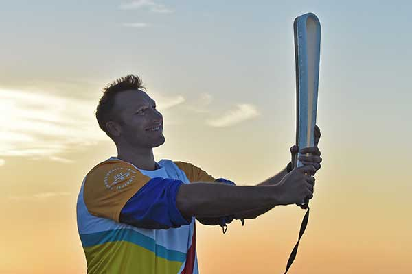 Ian Thorpe holding the Queens Baton in front of sunset sky