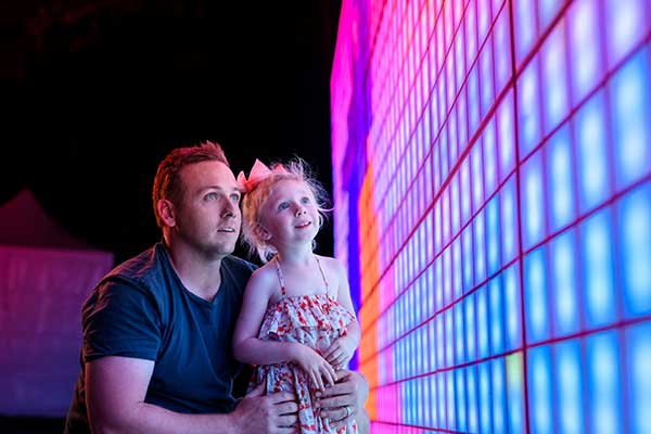 Mand and girl looking at coloured light wall