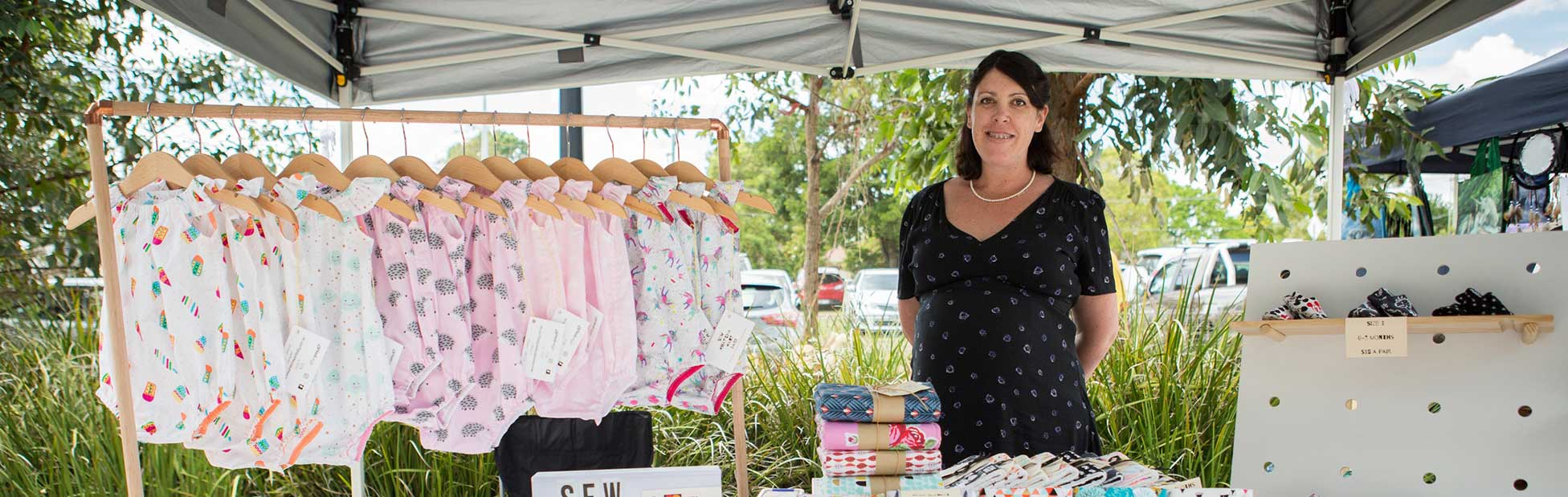 Woman stallholder selling baby clothing