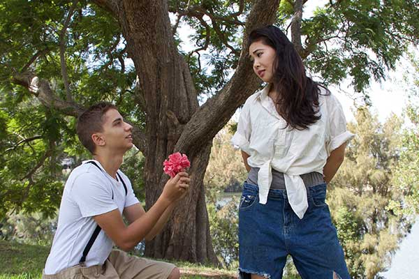Young man on his knees offering flower to young woman with riverside in background