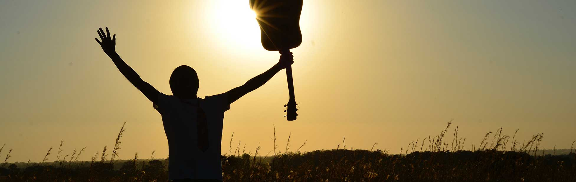 Person holding up guitar against sun in field