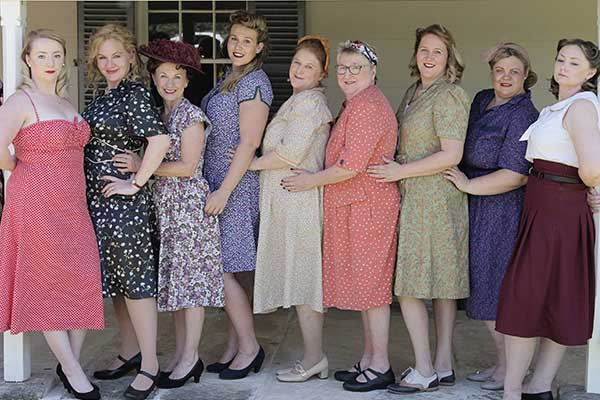 Women in a line all wearing 40's style dresses