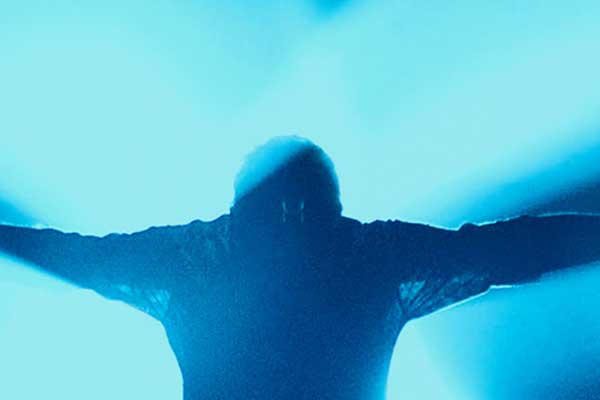 Blue back-lit silhouette of man arms out and head down