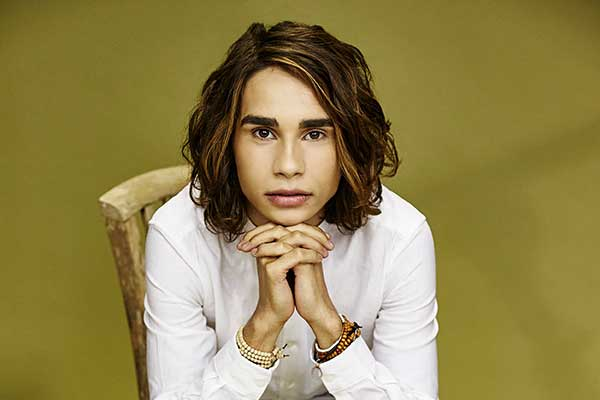 Isaiah Firebrace sitting on chair chin sitting on his hands