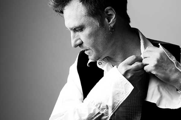John Waite in collared shirt and vest with hand to his neck