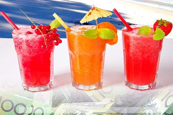 Three fruity cocktails lined up on a bar