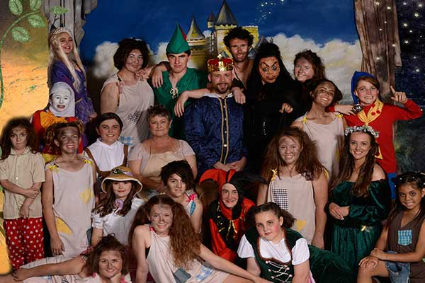 Cast of fairy tale in full dress posing for photo