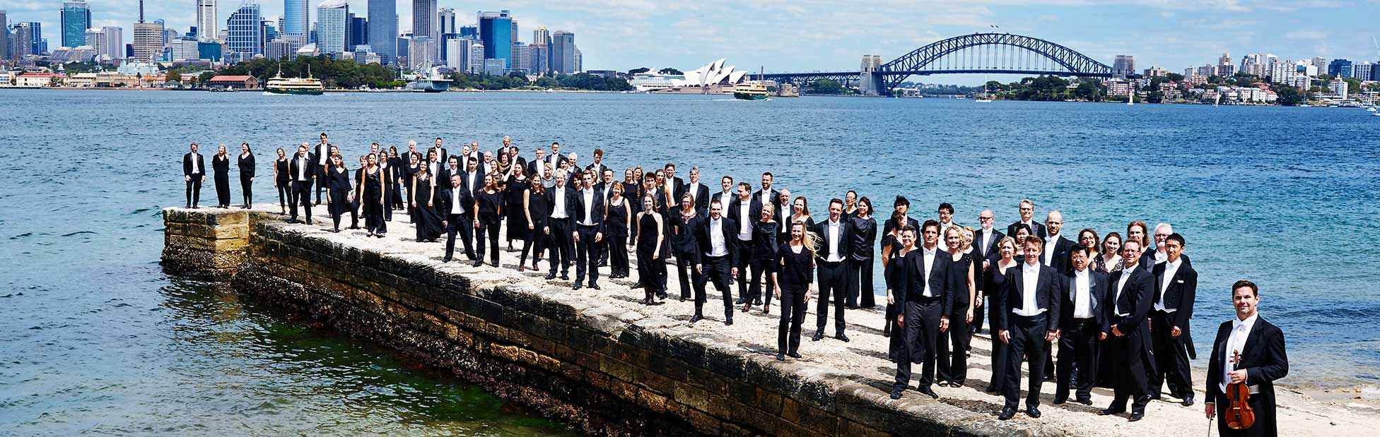 Orchestra posing for photo in front of Sydney Harbour Bridge