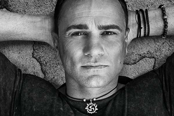 Shannon Noll lying on his back hands on head looking up