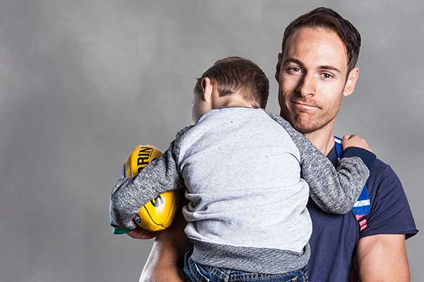 Man holding boy in hug embrace with football