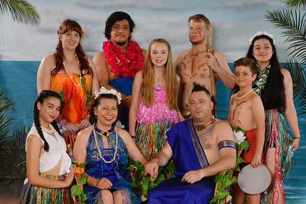 Cast posing in island style clothing