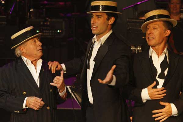 The men singing in hats with bow ties undone