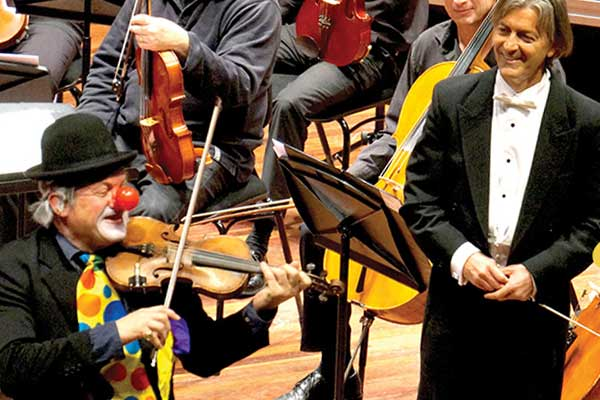 Clown playing violin with conductor watching and smiling
