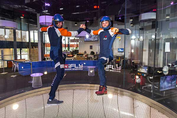 Two indoor skydivers performing