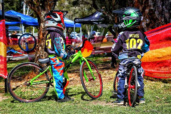 Children standing with BMX bikes wearing helmets and protective gear