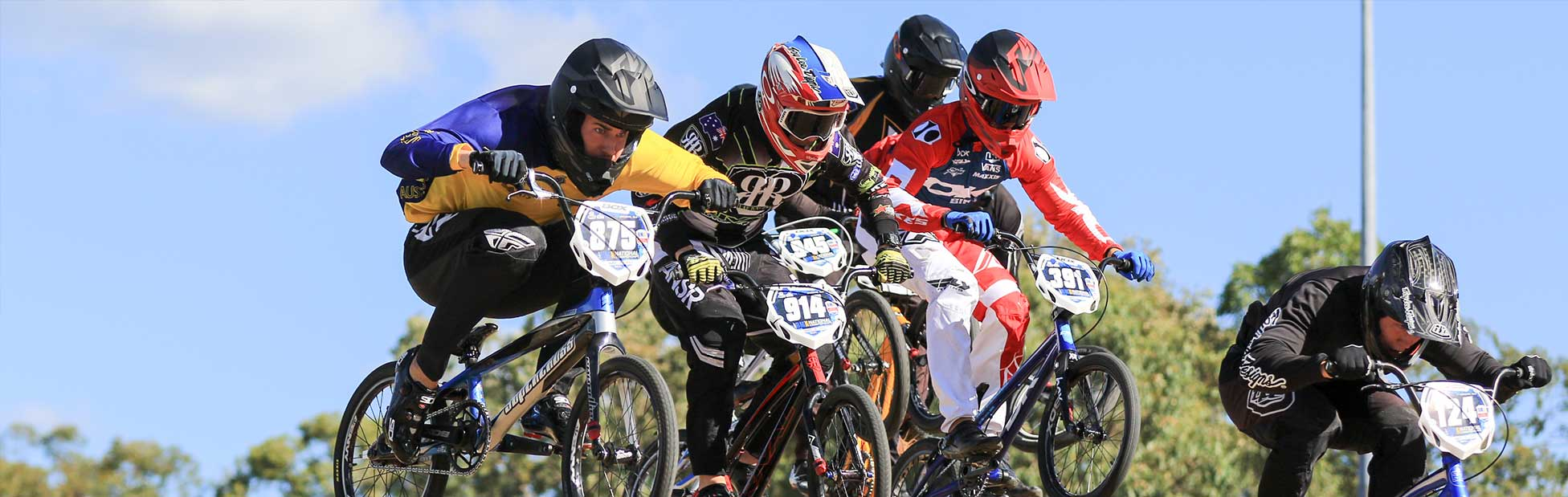 Five racing BMX riders on jump in full gear
