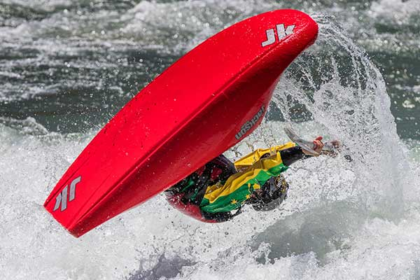 Competitor on the Whitewater mid somersault in red kayak