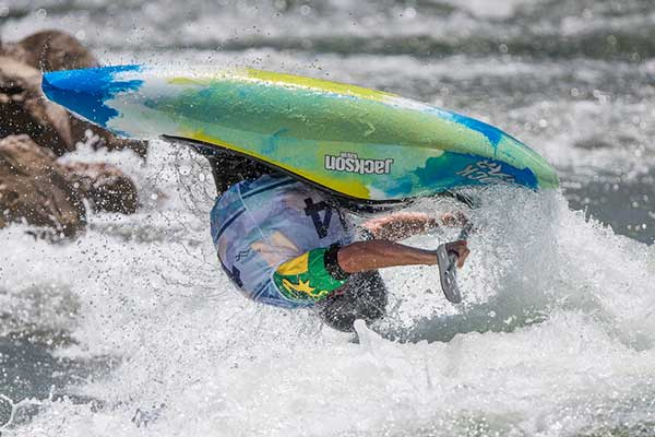 Male competitor in kayak mid somersault on the whitewater