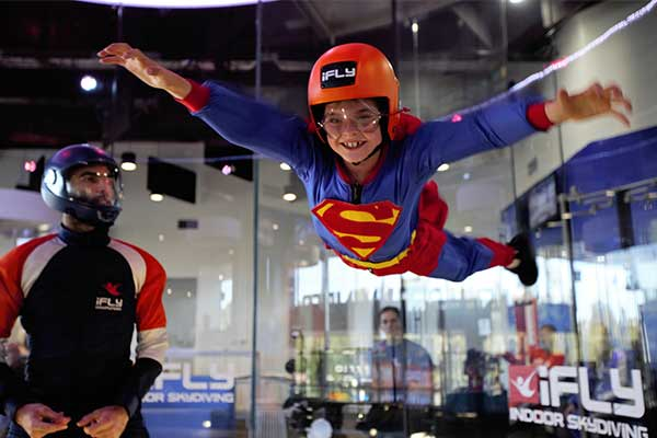 Child indoor skydiving wearing superman outfit