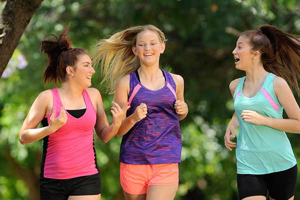 Three young women in jogging gear on Nepean River Parkrun