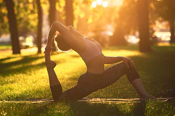 Woman in yoga pose with sunrise behind her