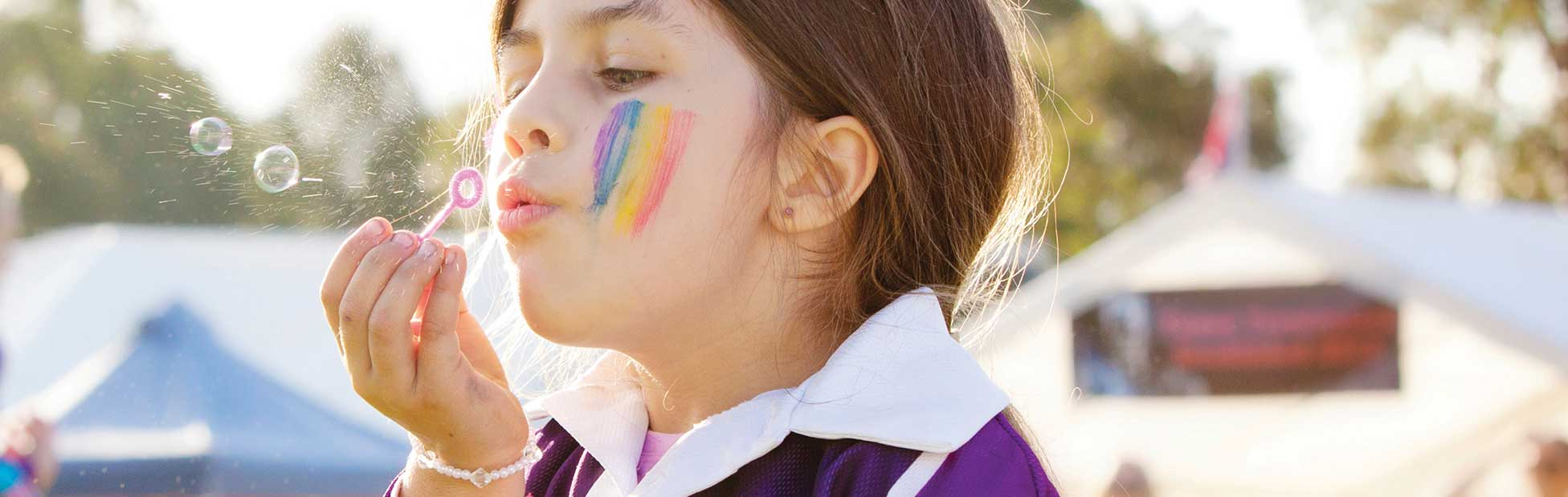 Young girl with rainbow painted on her face blowing bubbles