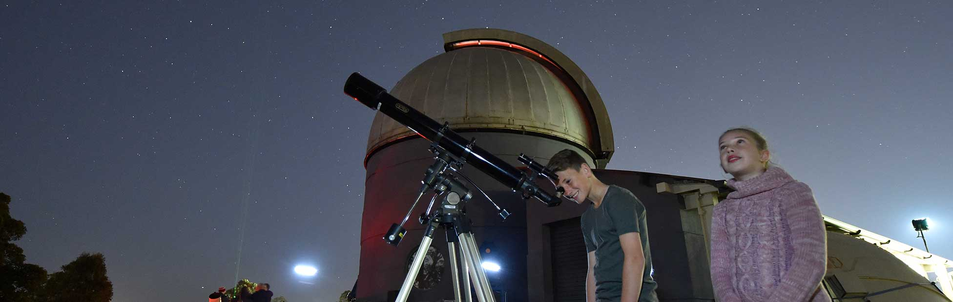 Boy looking through telescope, girl looking at sky with observatory behind them