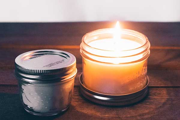 A lit candle in a jar