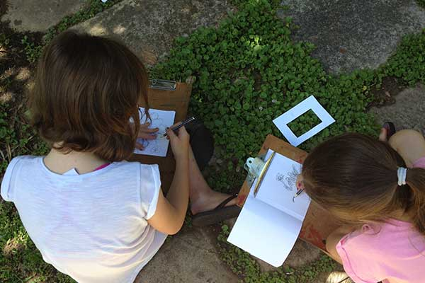 Girls in garden drawing on paper mounted on clipboards