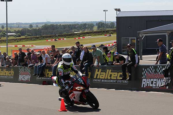 Motorcycle going around a cone on the racetrack audience watching