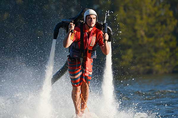 A young man hovering above the water using a water powered jet pack