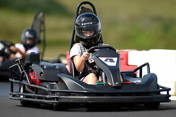 A young girl driving a go kart